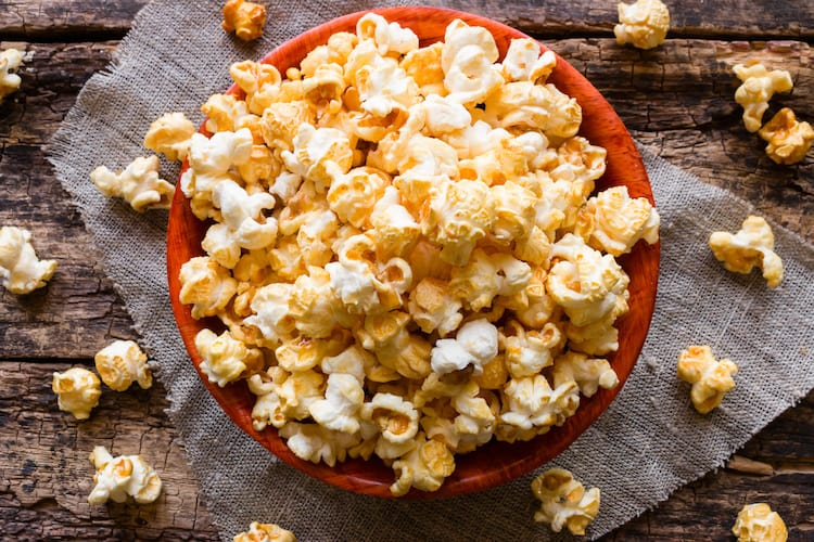 We love this easy homemade caramel popcorn recipe. It only requires a few inexpensive ingredients and it bakes in the oven til it's crispy!